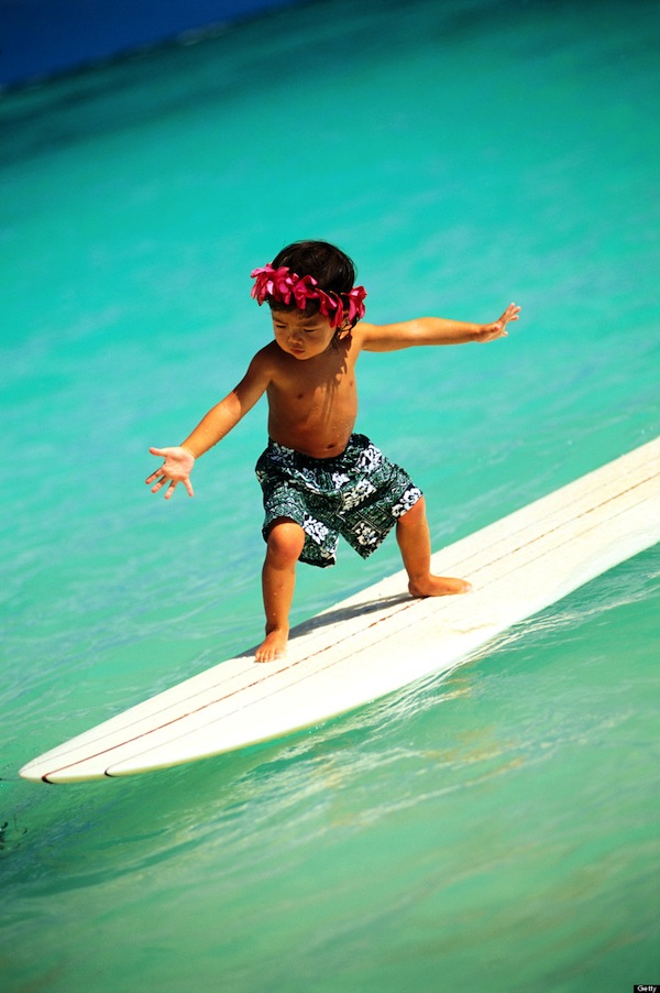 Closeup of little local boy on white surfboard, arms spread, pink haku, turquoise water